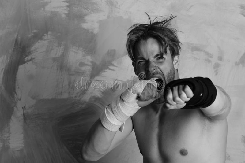 Guy with black kimono belt and bandage on arms. Man with wild face and naked torso on colorful background. Boxer or karate fighter practices martial arts royalty free stock image