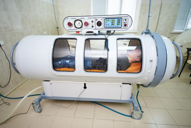 The guy in the black T-shirt lies in the hyperbaric chamber. Oxygen therapy, medical room royalty free stock photos