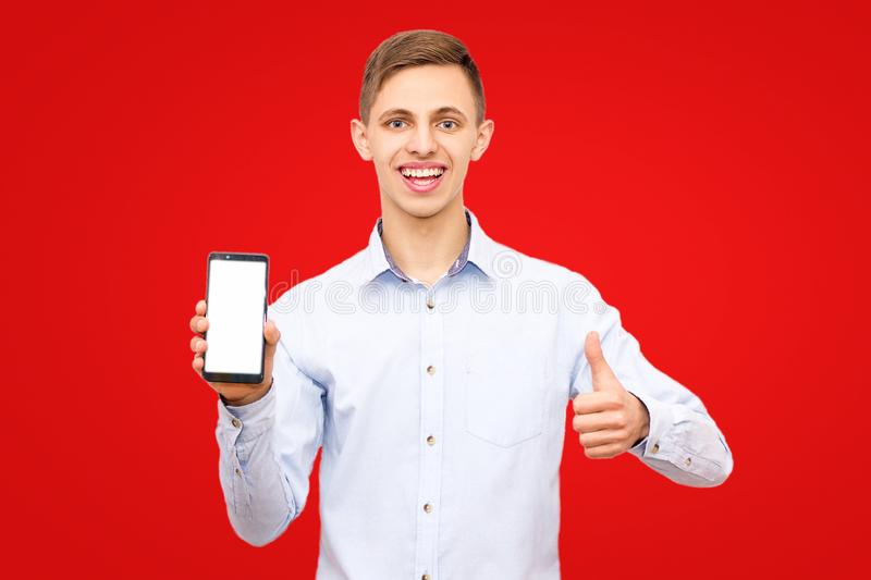 Guy in a blue shirt advertises a phone isolated on a yellow background in the studio stock photography