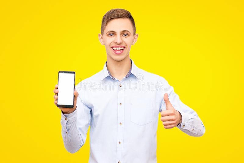 Guy in a blue shirt advertises a phone isolated on a yellow background in the studio stock images