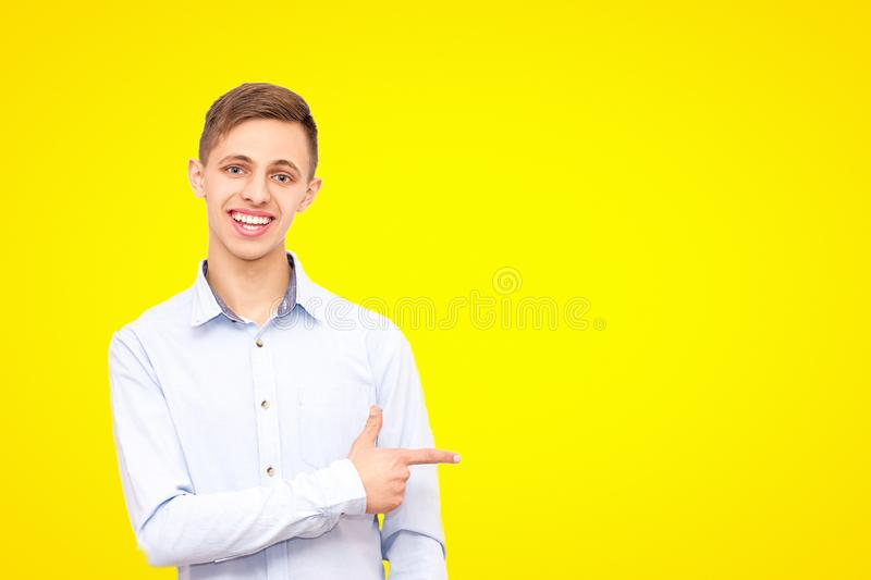 A guy in a blue shirt advertises a product, isolated on a yellow background stock image