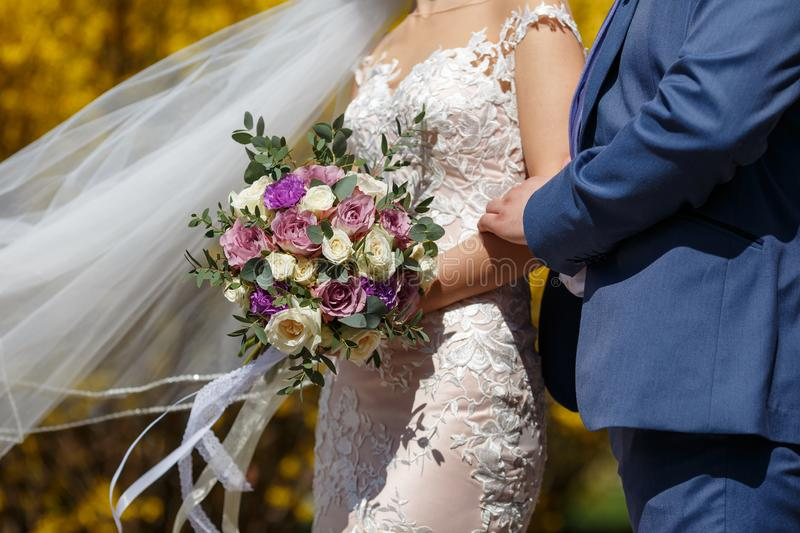 Guy in a blue suit and a girl in a white rose lase wedding dress with a bouquet of violet flowers and greens in hands stand in the stock photos
