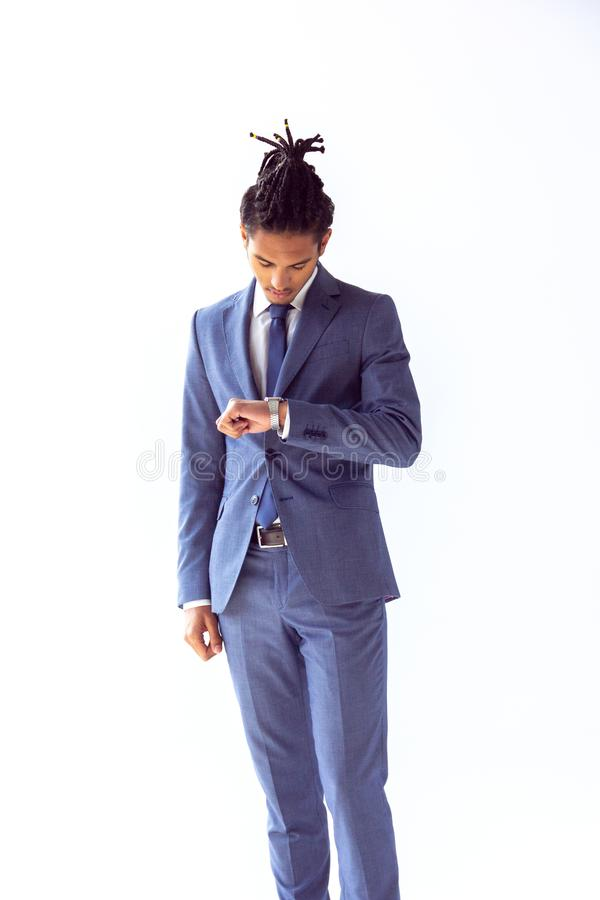 A guy in a blue suit looks at his watch worriedly stock photography