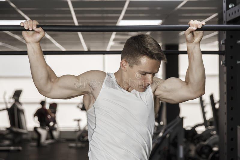 Guy bodybuilder execute exercise pulling up on horizontal bar in gym, horizontal photo.  stock photography