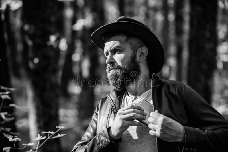 Guy brutal bearded cowboy drink alcohol metal flask. Hipster with beard drink alcohol nature background defocused. Guy brutal bearded cowboy drink alcohol metal stock images