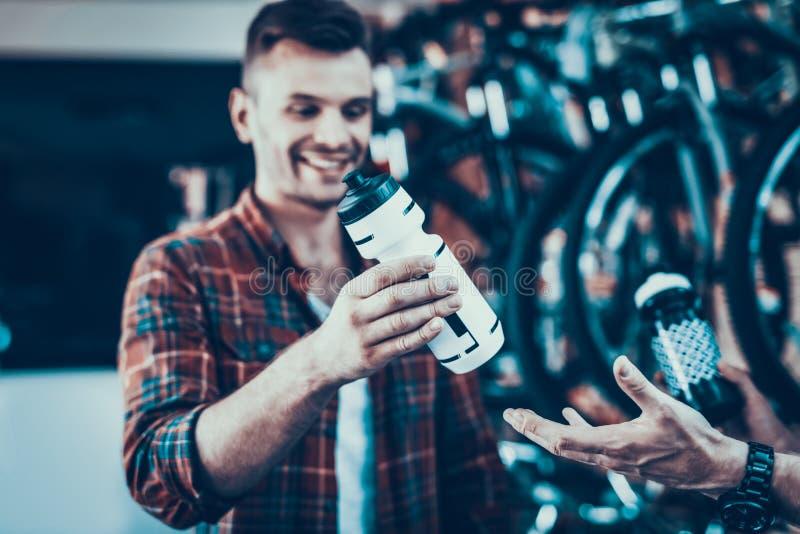 Guy Buy New Water Bottle para a bicicleta na loja da bicicleta imagem de stock