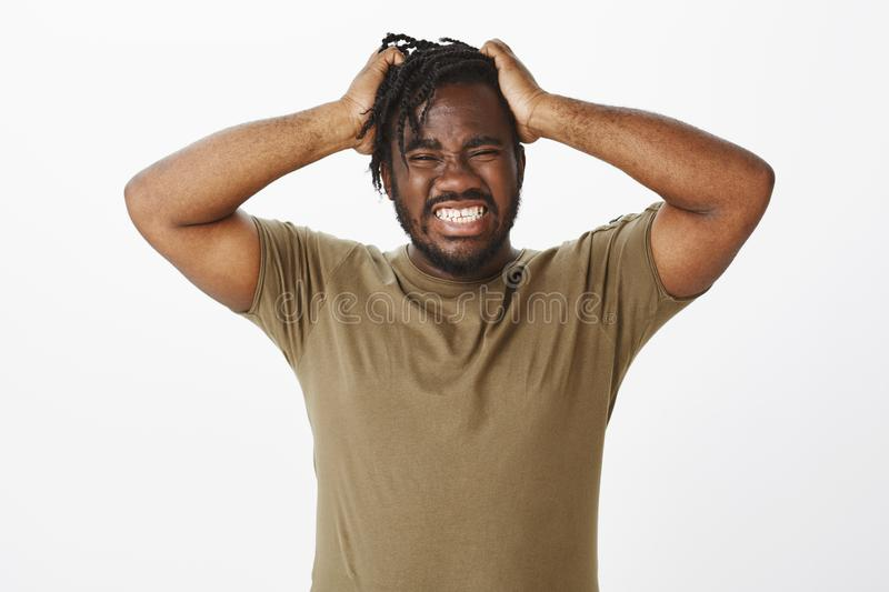 Guy cannot hold negative emotions inside. Depressed desperate african american man in olive t-shirt, holding hands on stock images