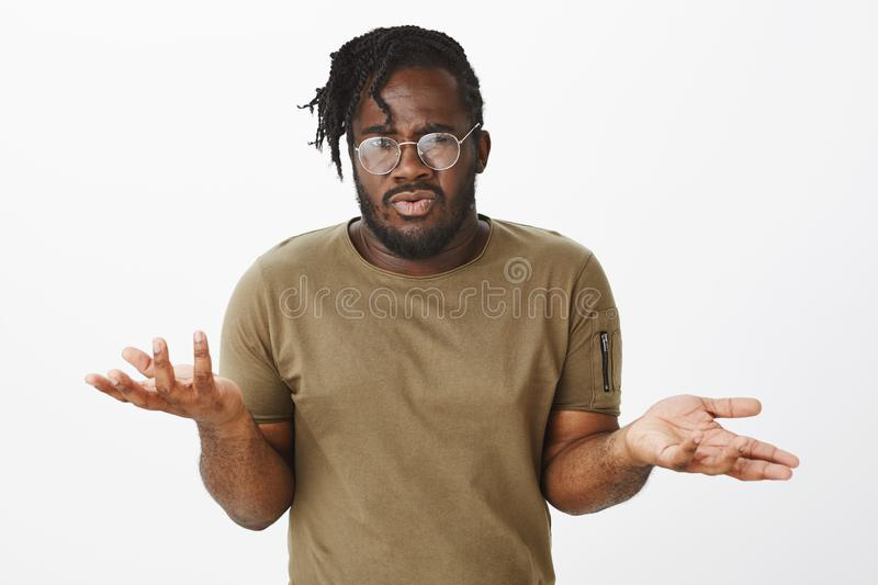 Guy cannot understand what girlfriend wants. Portrait of confused displeased dark-skinned man in casual outfit, raising. Palms and shrugging while being royalty free stock photos
