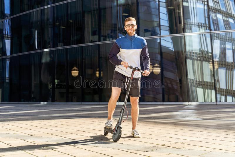Guy cares about environment and travels on scooter royalty free stock photo