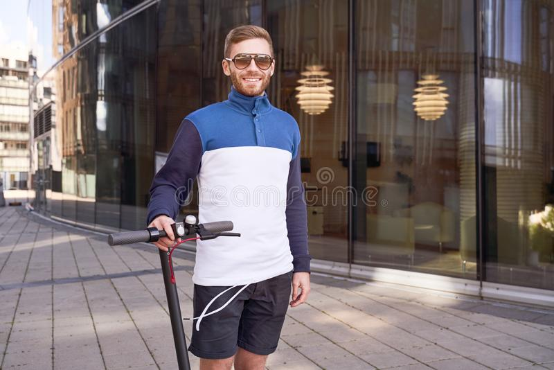 Guy cares about environment and travels on scooter royalty free stock image