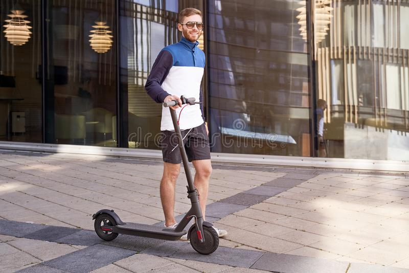 Guy cares about environment and travels on scooter royalty free stock images