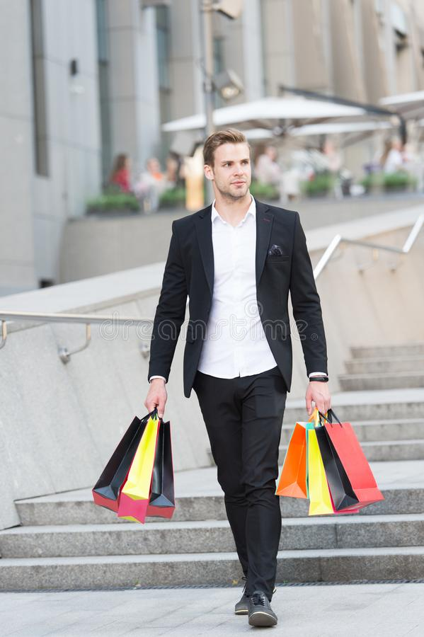 Guy carry bunch shopping bags. Profitable deals shopping on black friday. Man hold lot paper bags packages after stock images