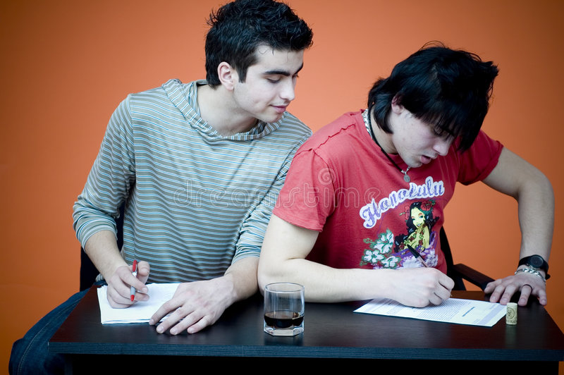 Guy cheating on exam. A view of one guy sitting at a table, looking over the shoulder of a second guy, copying answers on a exam royalty free stock images