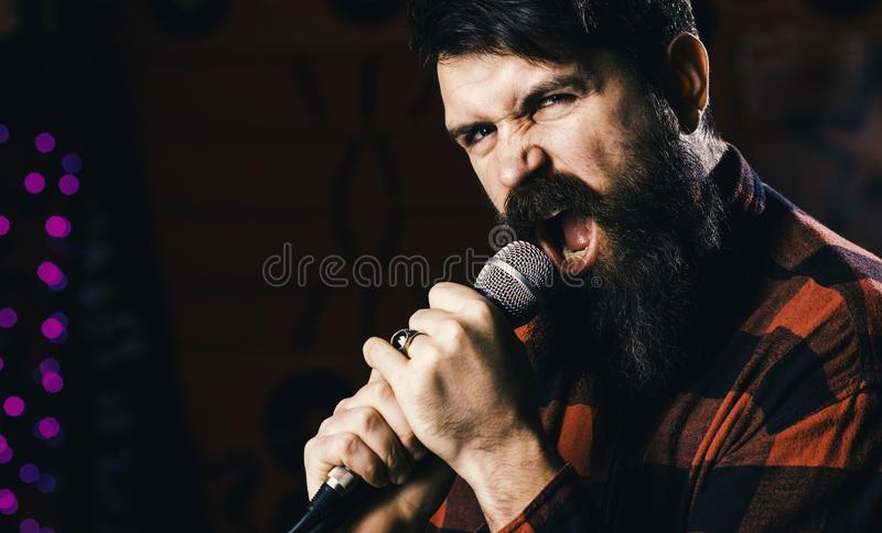 Guy in checkered shirt on black background, defocused. Young man singing with microphone. Hipster with beard royalty free stock photo