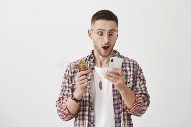 Guy checks his bank account via smartphone. Portrait of shocked good-looking man in glasses holding credit card and stock images