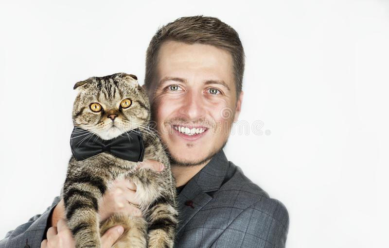 Guy in the classic fashionable suit with a cat in a bow tie on a white background stock photo