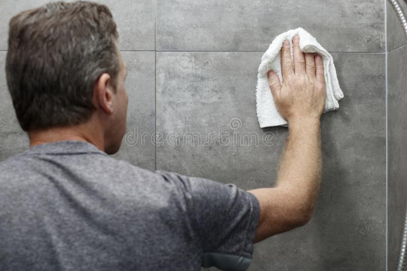 Guy Cleaning Gray Tile Bathroom Shower Wall com um pano imagem de stock