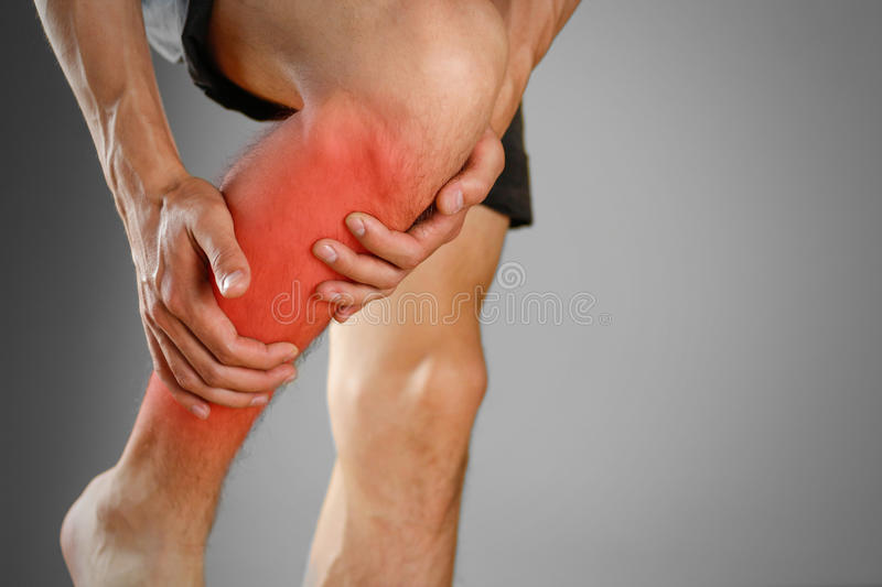 The guy clings to a bad knee. The pain in his leg. Closeup. The. Lesion is highlighted in red stock photography
