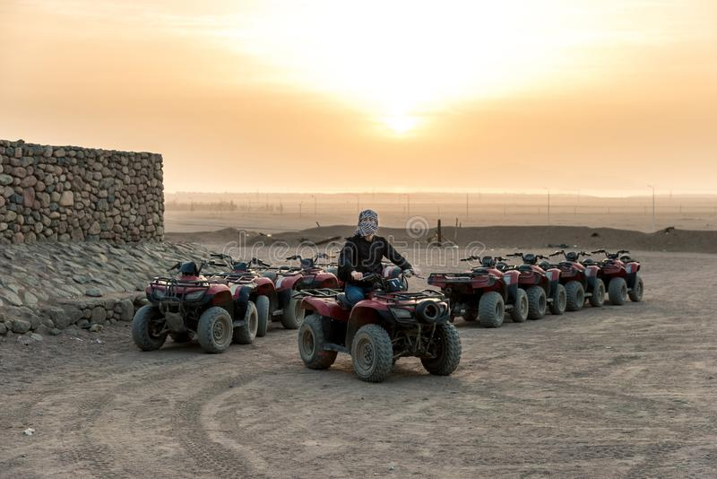 A guy with a closed handkerchief on his face sits on a quad bike against the backdrop of the sun rising over the desert. Horizontal frame stock photo