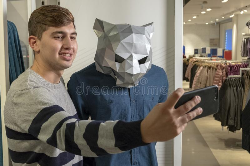A guy in a clothing store makes a funny selfie with a mannequin. Animal shopping with a phone in their hands. stock photography