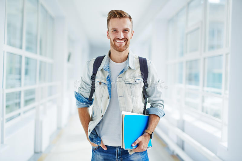 Guy in college. Clever student with books looking at camera with smile royalty free stock images