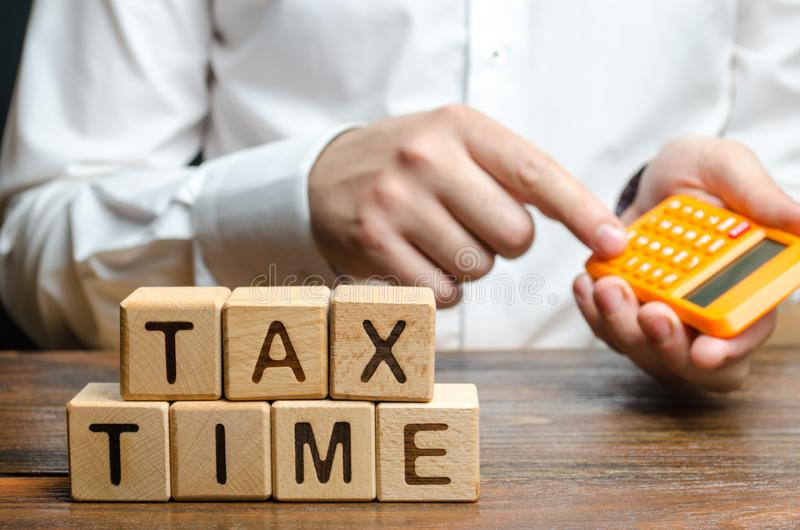 The guy counts on the calculator the necessary tax payment. Taxation, income tax. Declaring income, countering the shadow economy. Digitalization of the royalty free stock photography