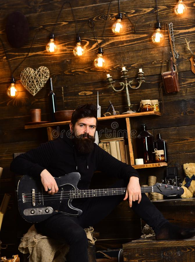 Guy in cozy warm atmosphere play relaxing soul music. Favourite activity. Man with beard holds black electric guitar. Man bearded musician enjoy evening with royalty free stock image