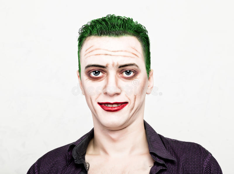 Guy with crazy joker face, green hair and idiotic smike. carnaval costume stock images