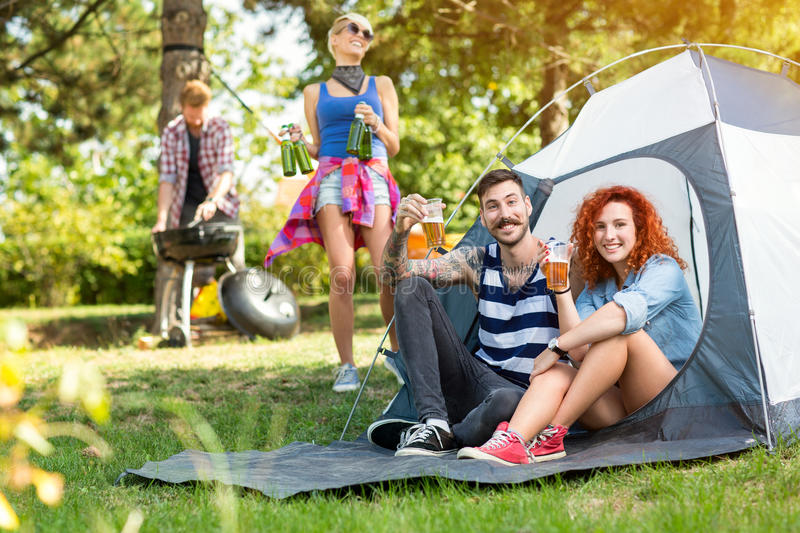 Guy and curly woman toast with glasses of beer. Young guy and curly ginger women toast with glasses of beer in front of tent at camping in woods royalty free stock photos