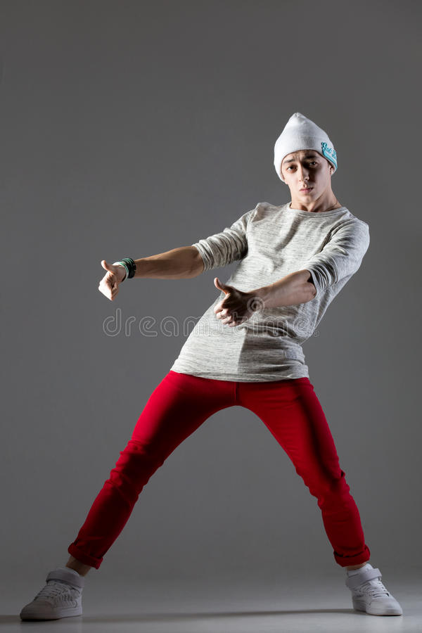 Guy dancing in beanie. Portrait of one teen funny hipster guy dancing, warming up wearing casual red jeans and beanie. Modern street style young dancer man stock photo