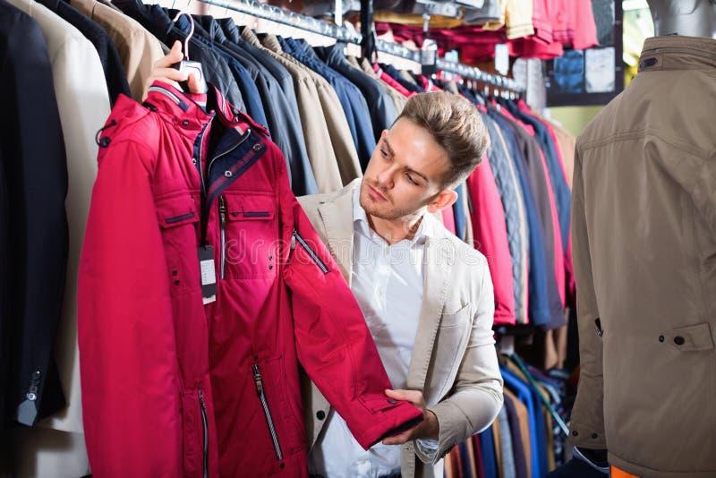 Guy deciding on warm coat in men's cloths store. Smiling cheerful positive guy deciding on warm coat in men's cloths store royalty free stock image