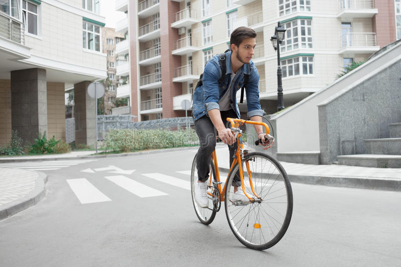 Guy in denim jacket goes to school on bike. Cyclists the road in the city. A guy in a blue denim jacket goes to school on an orange bike. Cyclists on the road in stock photography