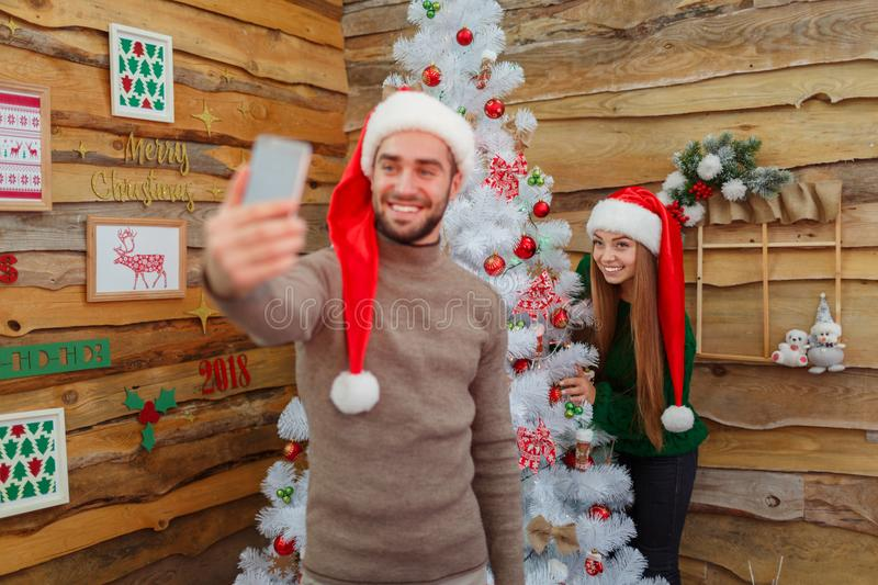The guy does selfie, the phone is out of focus, in the background with the girl happy and the Christmas tree in the room royalty free stock photography