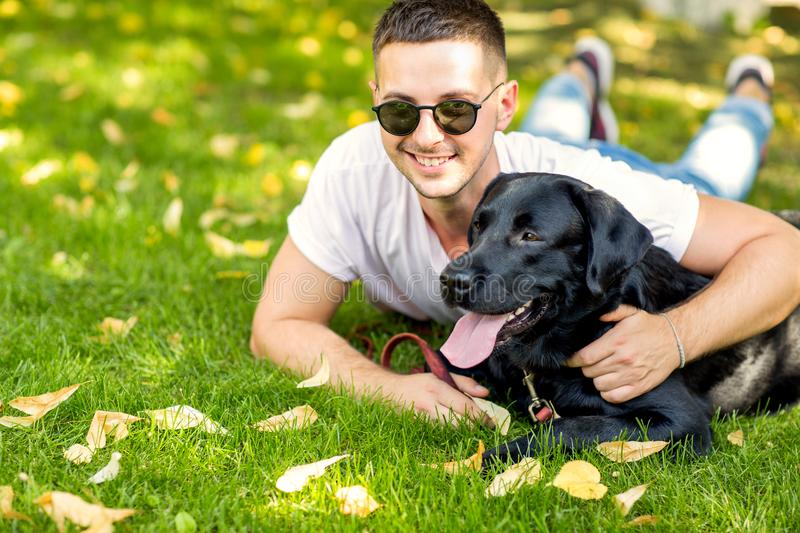 Guy with a dog labrador on the street playing stock image