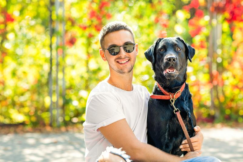 Guy with a dog walks in a park in autumn.  royalty free stock images