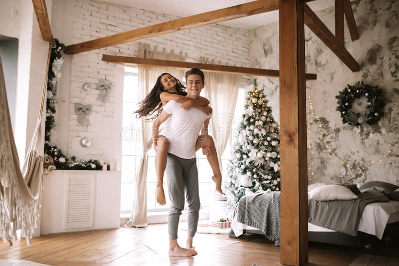 Guy dressed in white t-shirt and shorts keeps the girl on his back in a cozy decorated room with wooden beams, a New. Year tree, gifts and candles royalty free stock photo