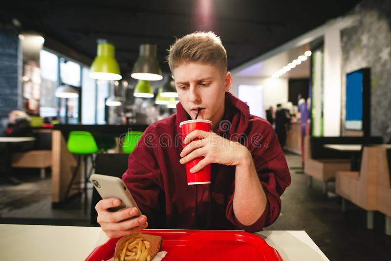 Guy drinks a beverage from a red glass and uses a smartphone in a fast food cafe stock photo