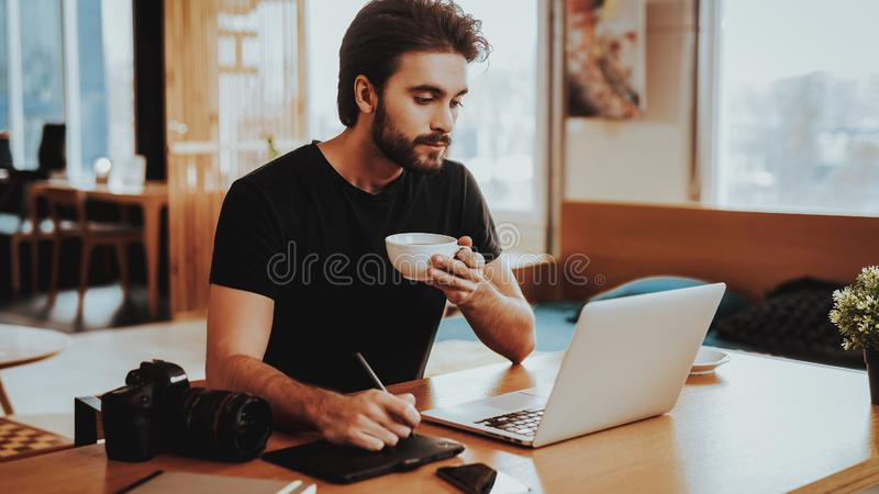 Guy Drinks Coffee While Working heureux sur l'ordinateur portable image stock