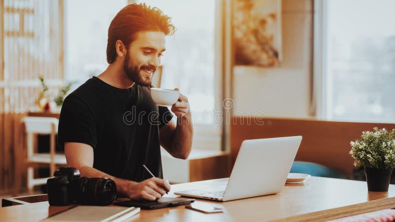 Guy Drinks Tea While Working de sourire sur l'ordinateur portable photographie stock