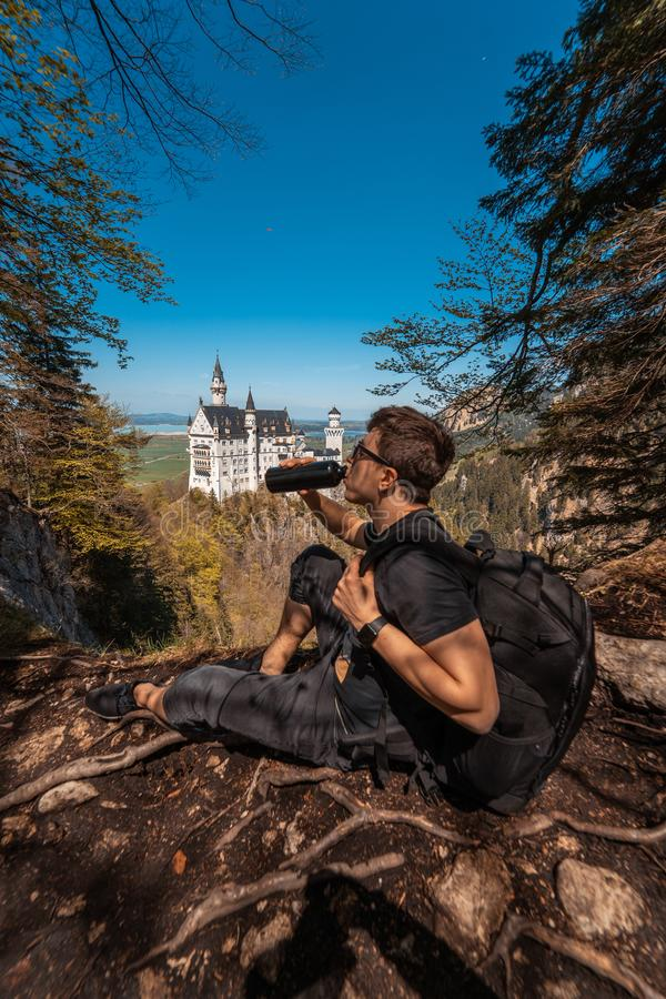 Guy drinks water on hill castle in the background stock photography