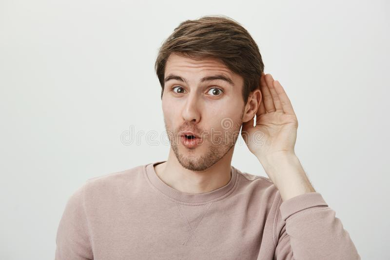 Guy enjoys put hit nose in business of other people. Thrilled handsome male holding palm near ear and saying wow. Overhearing conversation and wanting to stock photo