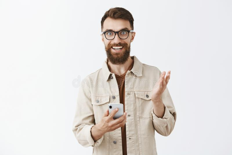 Guy excited of new smartphone features describing gadget to friends holding device in hands and gesturing with palm. Smiling thrilled and amused explaining royalty free stock photo