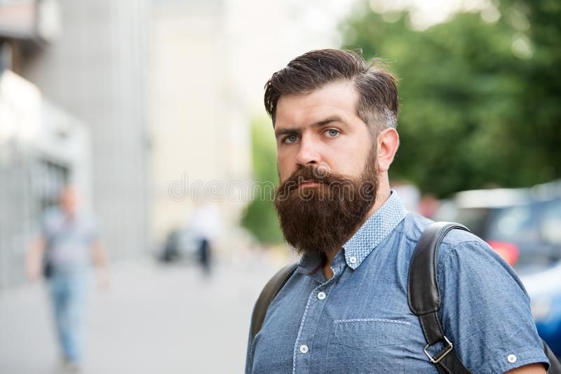 Guy exploring city. Comfortable tourism. Summer vacation. Hipster wearing backpack urban street background. Bearded man royalty free stock photography