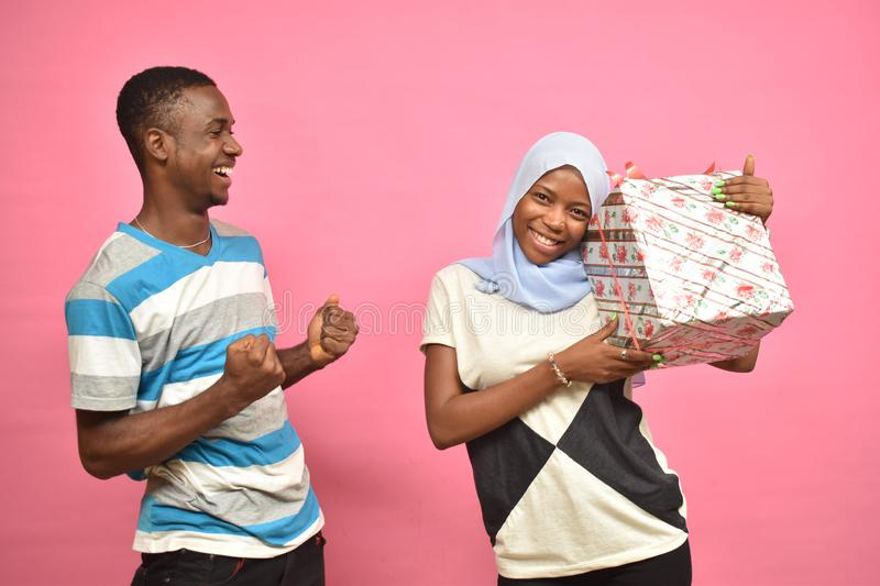 guy feeling excited with girlfriend after giving her a present stock photography