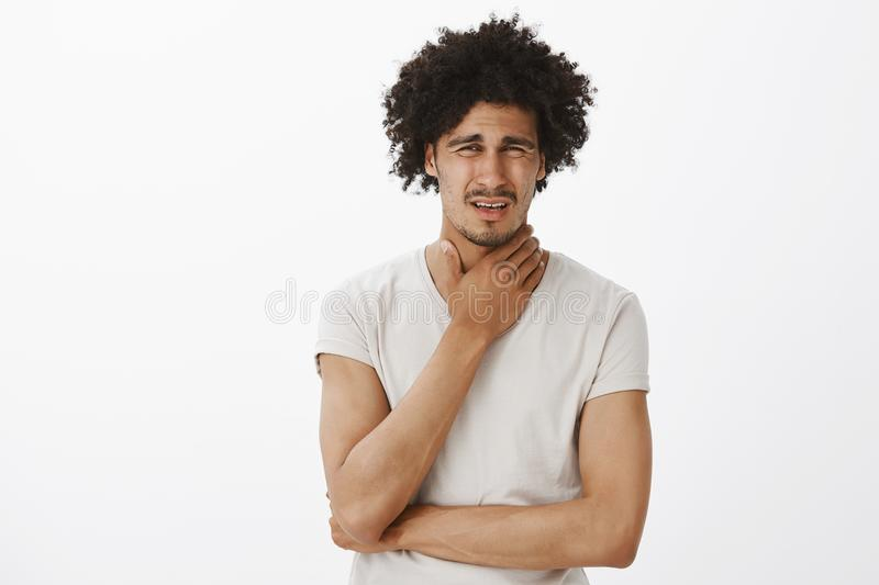 Guy feeling pain in throat, catching cold, frowning and grimacing from painful feeling, rubbing neck, standing intense. Over gray background, asking wife to royalty free stock images
