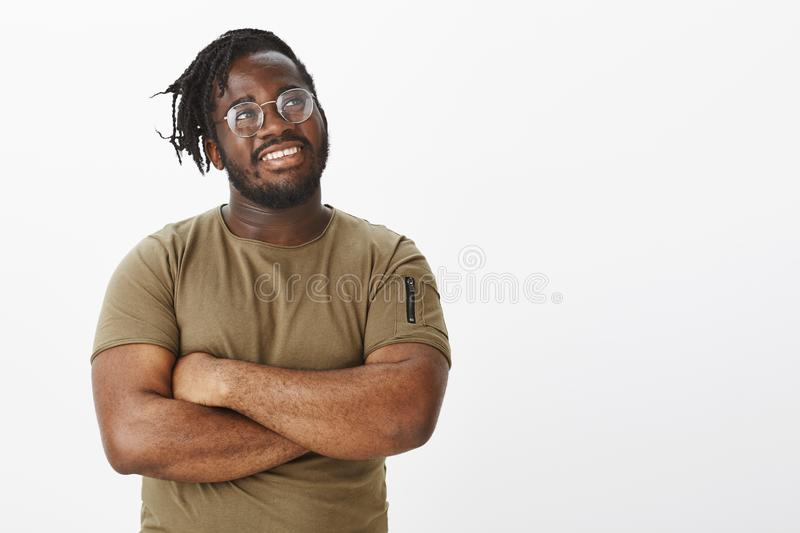 Guy feeling proud finishing work in time. Happy dreamy african american plump man with beard in t-shirt and glasses. Holding hands crossed and gazing with royalty free stock photography