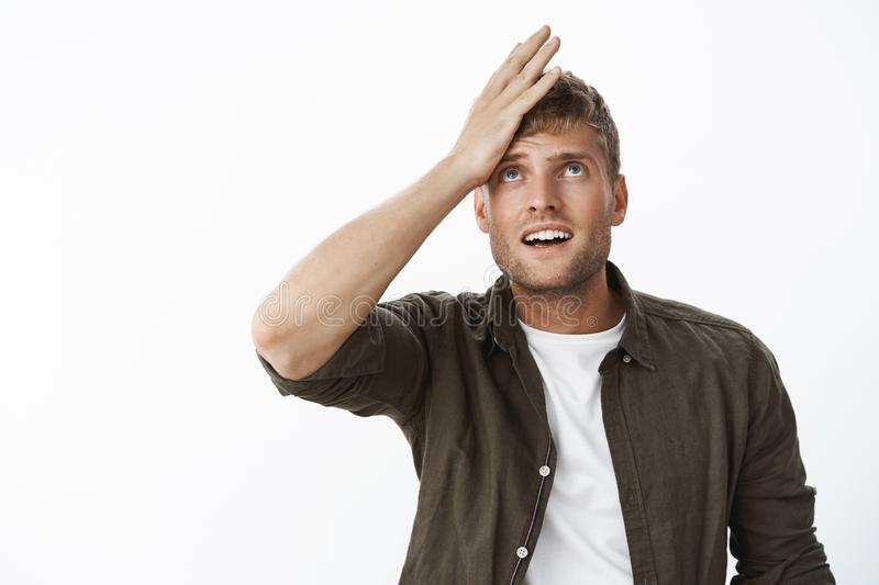 Guy feeling upset and regret as forgetting something, cannot recall information holding palm on forehead looking up. Thinking, cannot remember important thing royalty free stock photos
