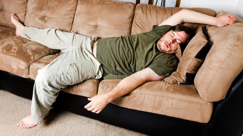 A guy flung all over the couch. MAn sleeping on the couch just all flung about stock photo