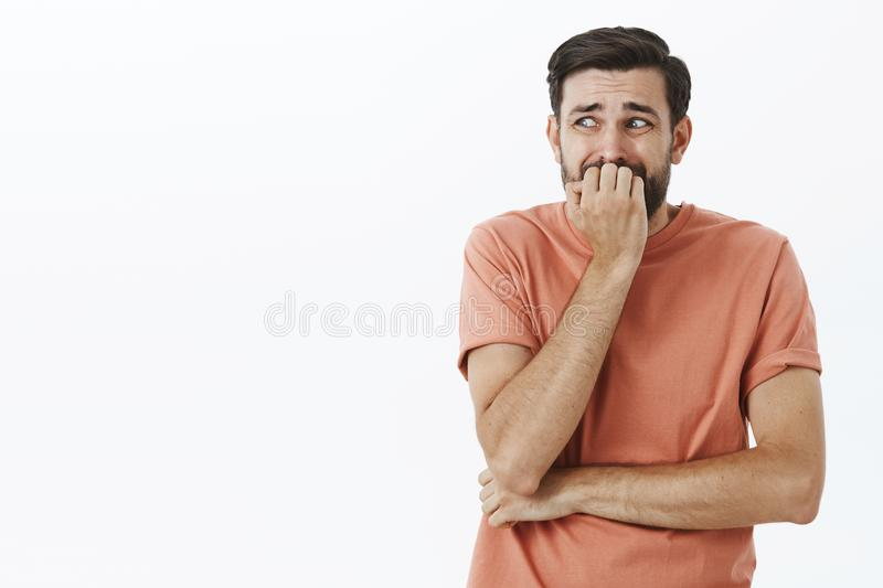 Guy freaked out and scared to death, trembling from fear standing insecure like coward, biting fingernails looking left stock images