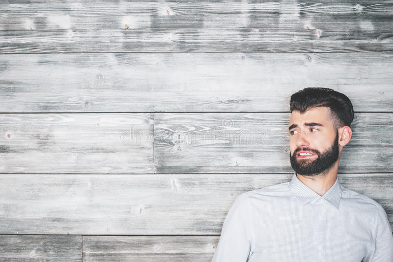 Guy with funny face. Portrait of handsome caucasian guy with funny expression on wooden wall background. Emotion concept royalty free stock photography